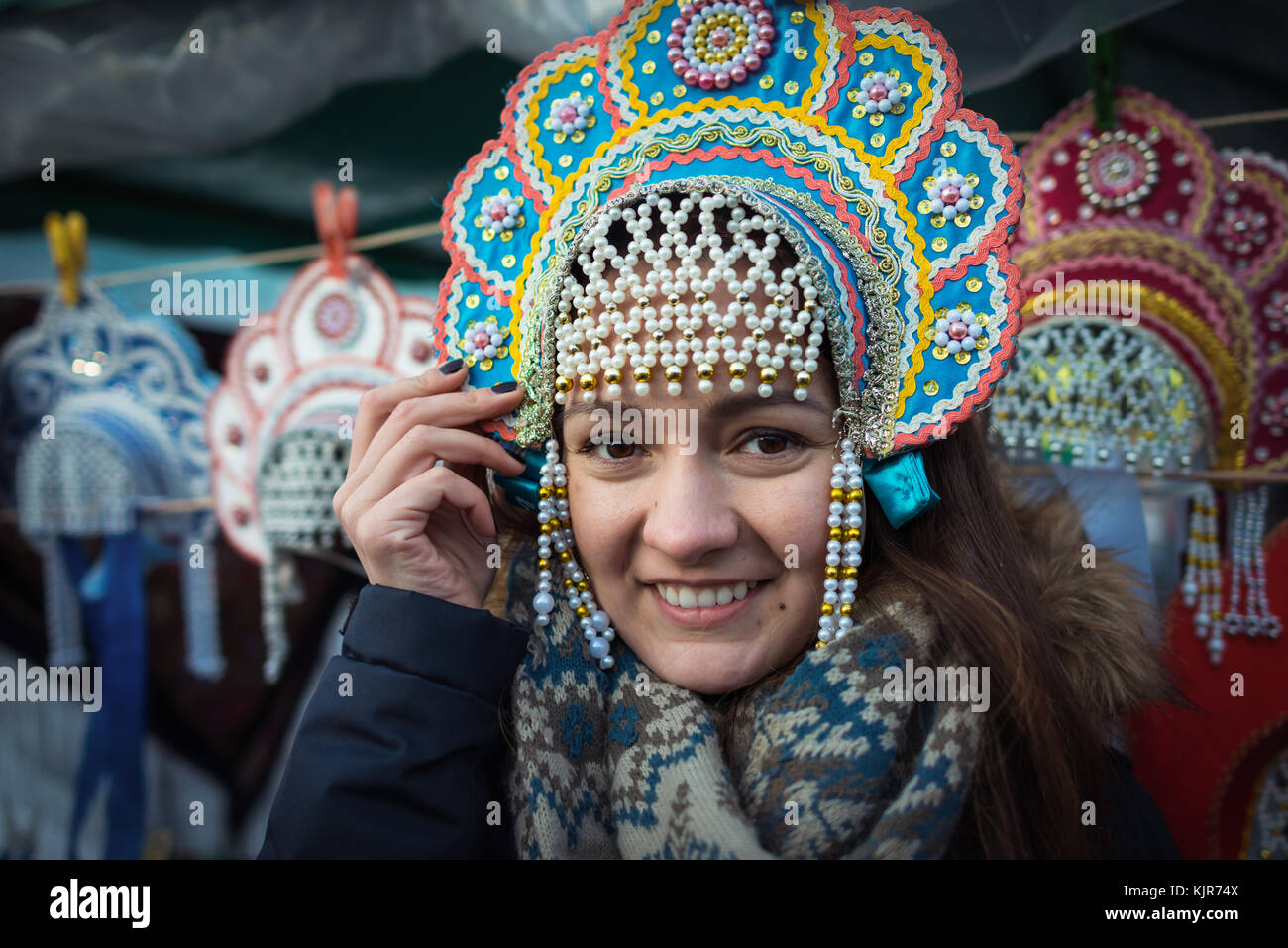 Cute and beautiful girl in warm and wool scarf smiling and standing at city market in national traditional headdress - Stock Image