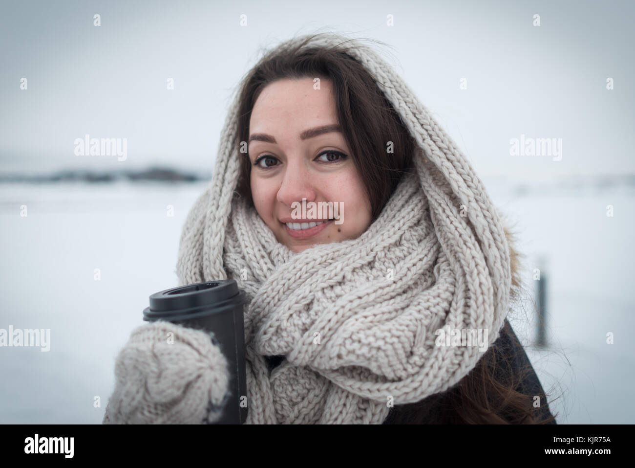Young woman in warm and soft scarf with hot coffee in cup for take away staying at clear field on the winter background. - Stock Image