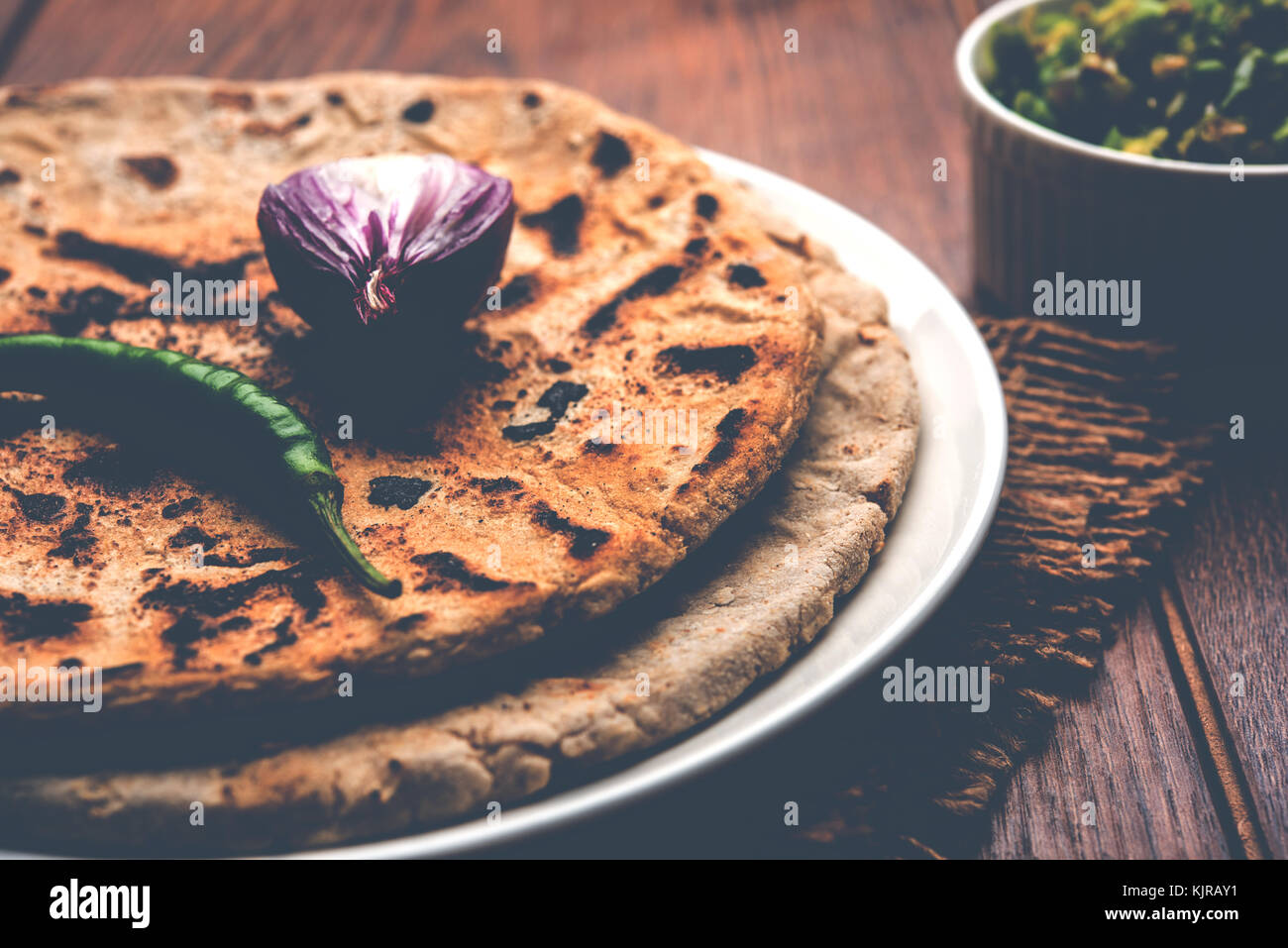 Bajra roti or Jowar Roti or Indian bread made using Bajra or Jowar, served with green chilly thecha - Stock Image