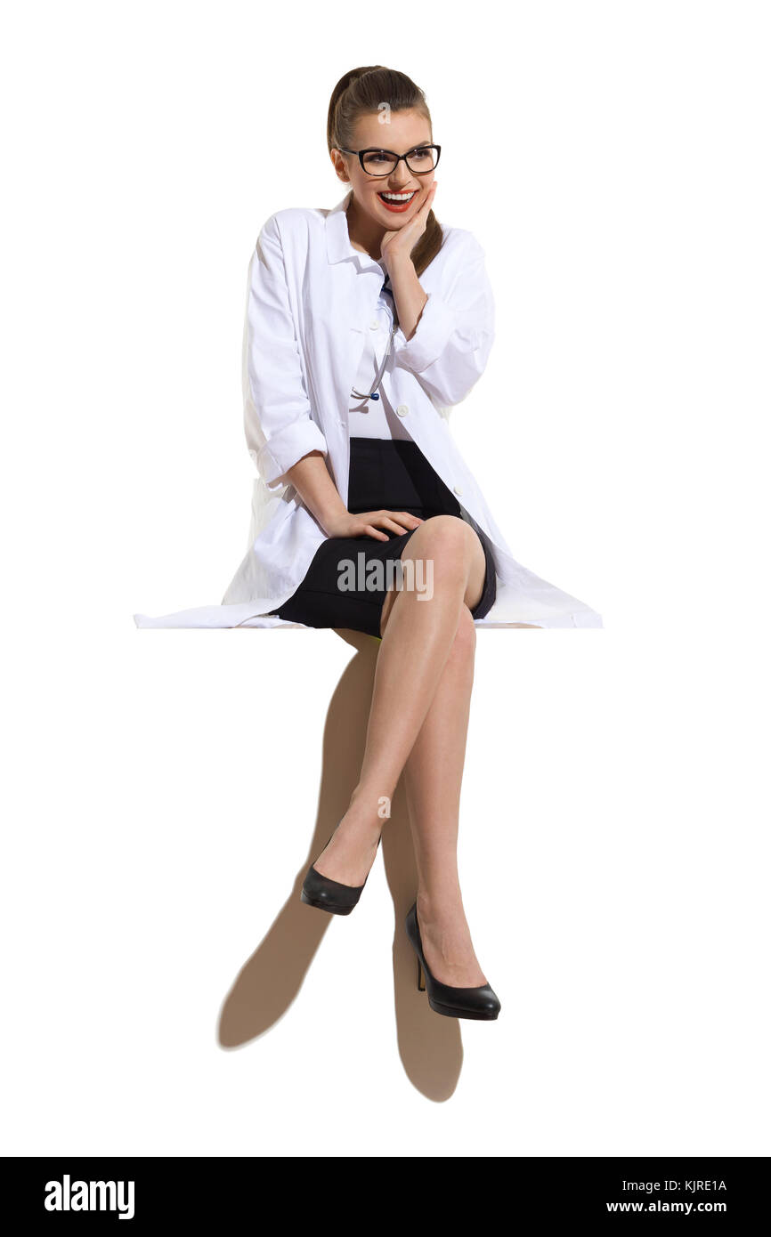 Excited young woman in glasses, white coat, black skirt and high heels sitting on a big white banner and holding - Stock Image