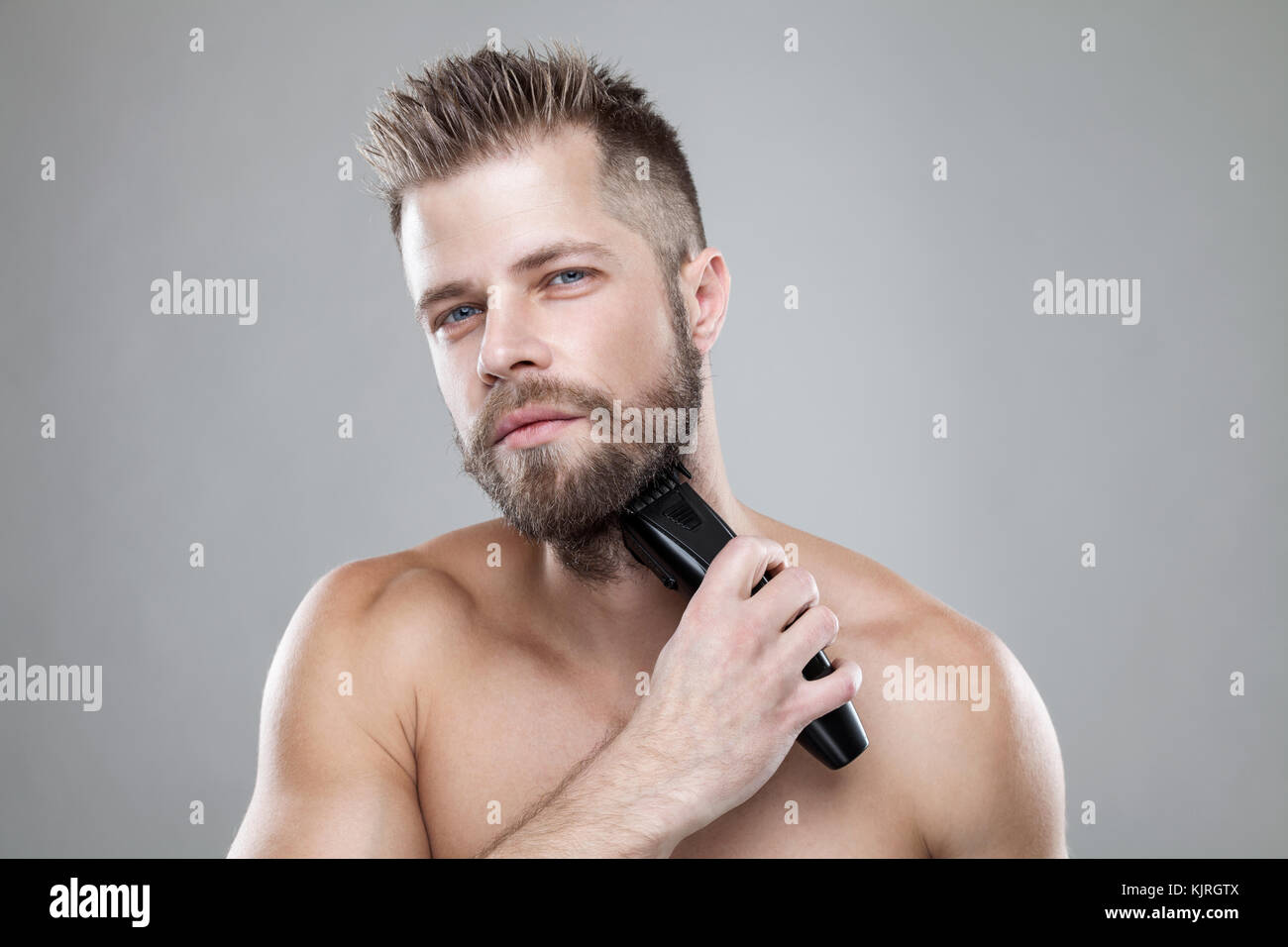 Handsome young bearded man trimming his beard with a trimmer - Stock Image