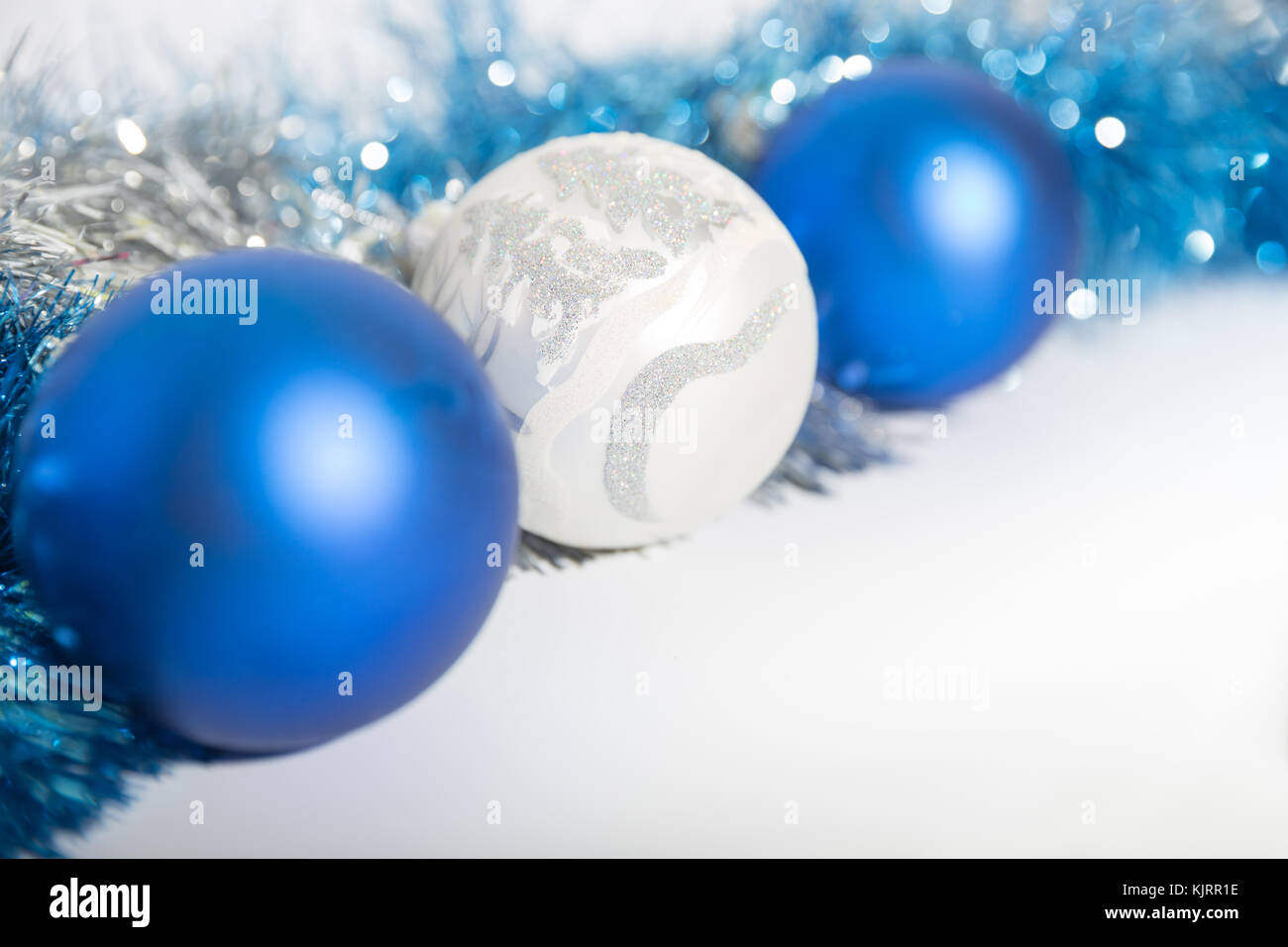 christmas decorations of blue and silver on a white background three balls and a tinsel - Blue And Silver Christmas
