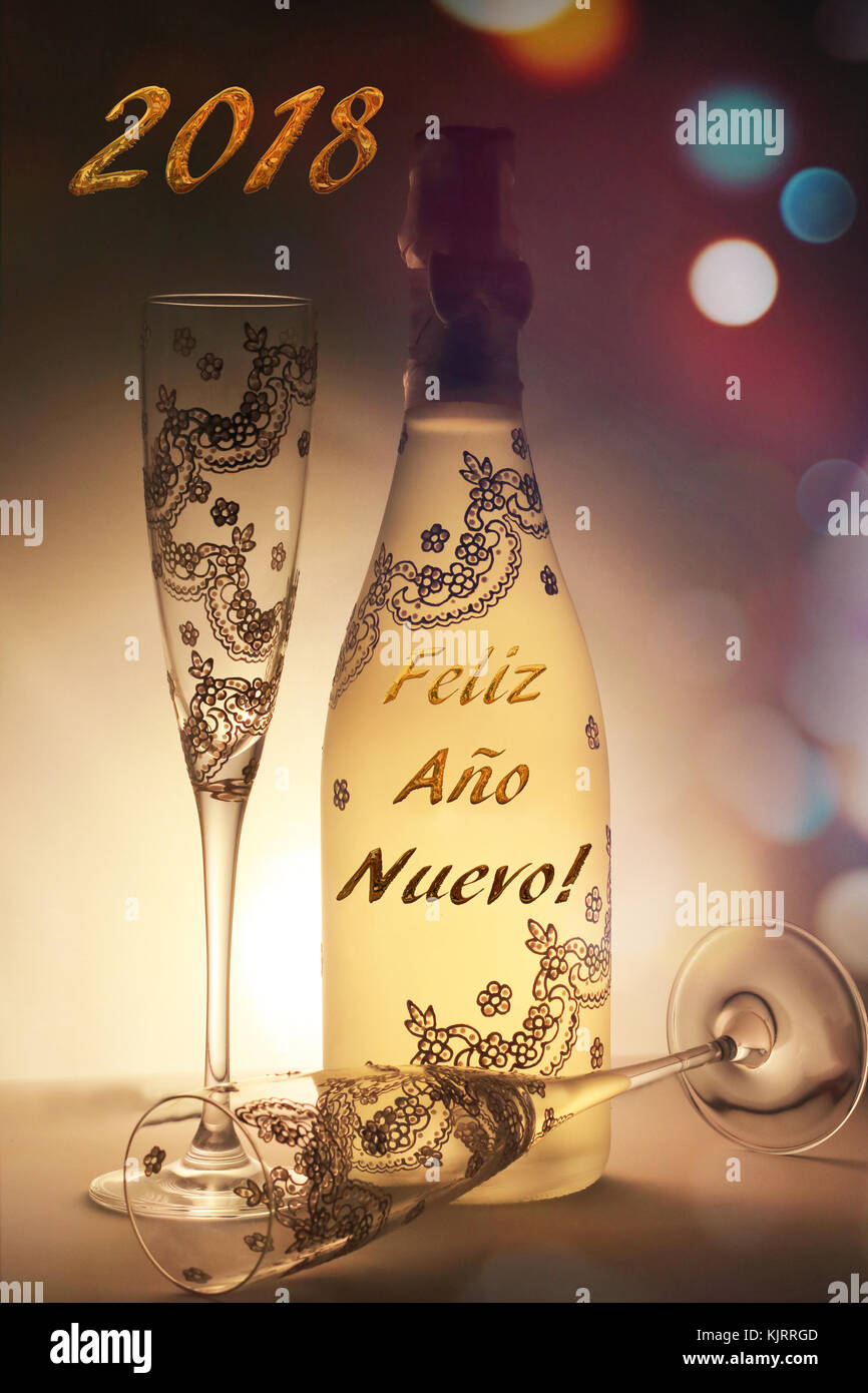 Champagne bottle and cup very nicely decorated with the message Happy New Year, written in Spanish, and surrounded - Stock Image