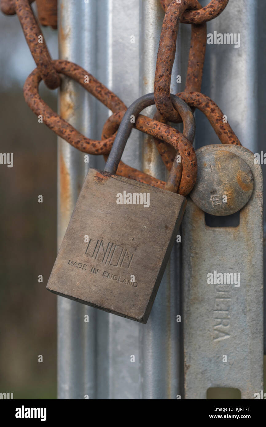 Padlock and chain securing industrial gate. Metaphor for security - email, data, identity, secure online payments, - Stock Image