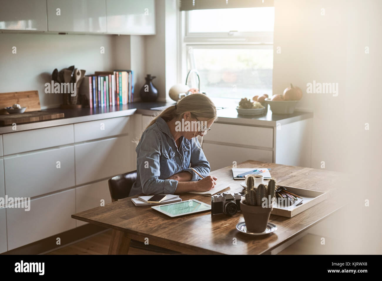Young woman sketching out designs with a pencil on a notepad while sitting at her kitchen table at home - Stock Image