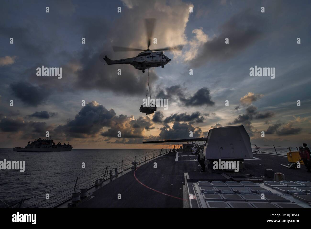 A U.S. Navy SA-330 Puma helicopter delivers cargo to the U.S. Navy Arleigh Burke-class guided-missile destroyer - Stock Image