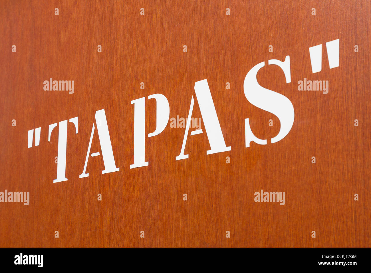 Large stencil 'Tapas' letters on an orange wall - Stock Image