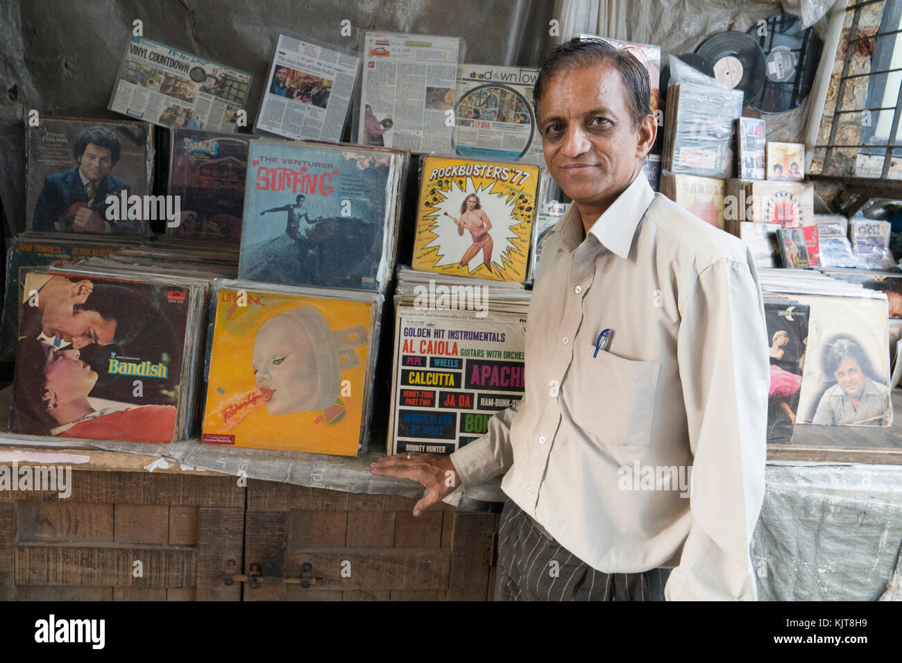 Man stands next to his second hand vinyl LP record stall in central Mumbai - Stock Image