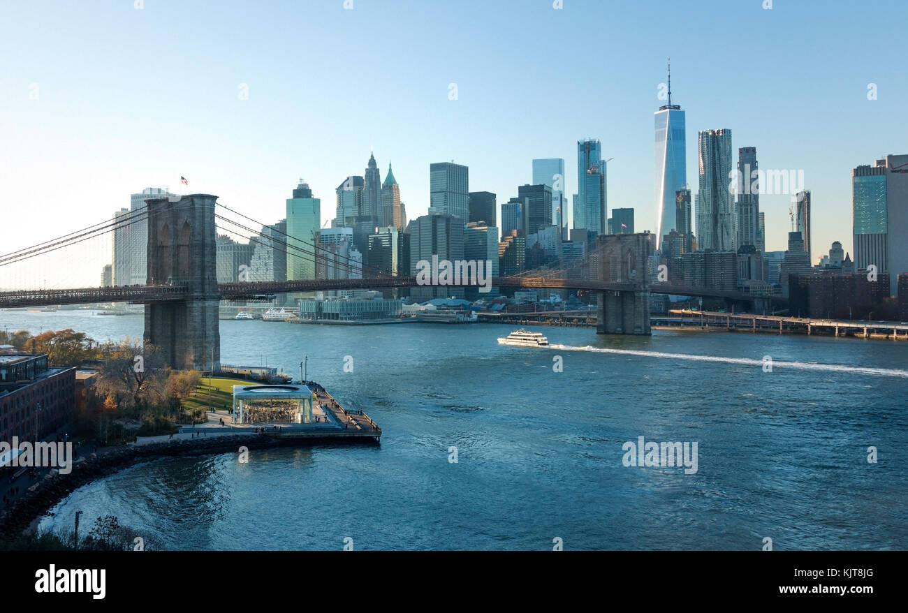 East River Ferry passing under the Brooklyn Bridge with the Lower Manhattan skyline in the background - Stock Image