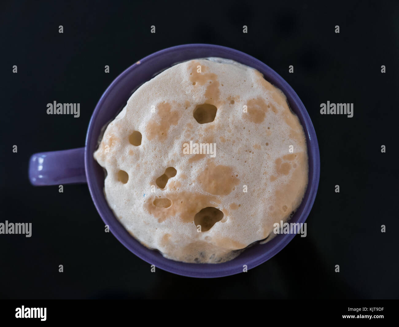 Close up of baker's yeast in a purple cup on black background. - Stock Image