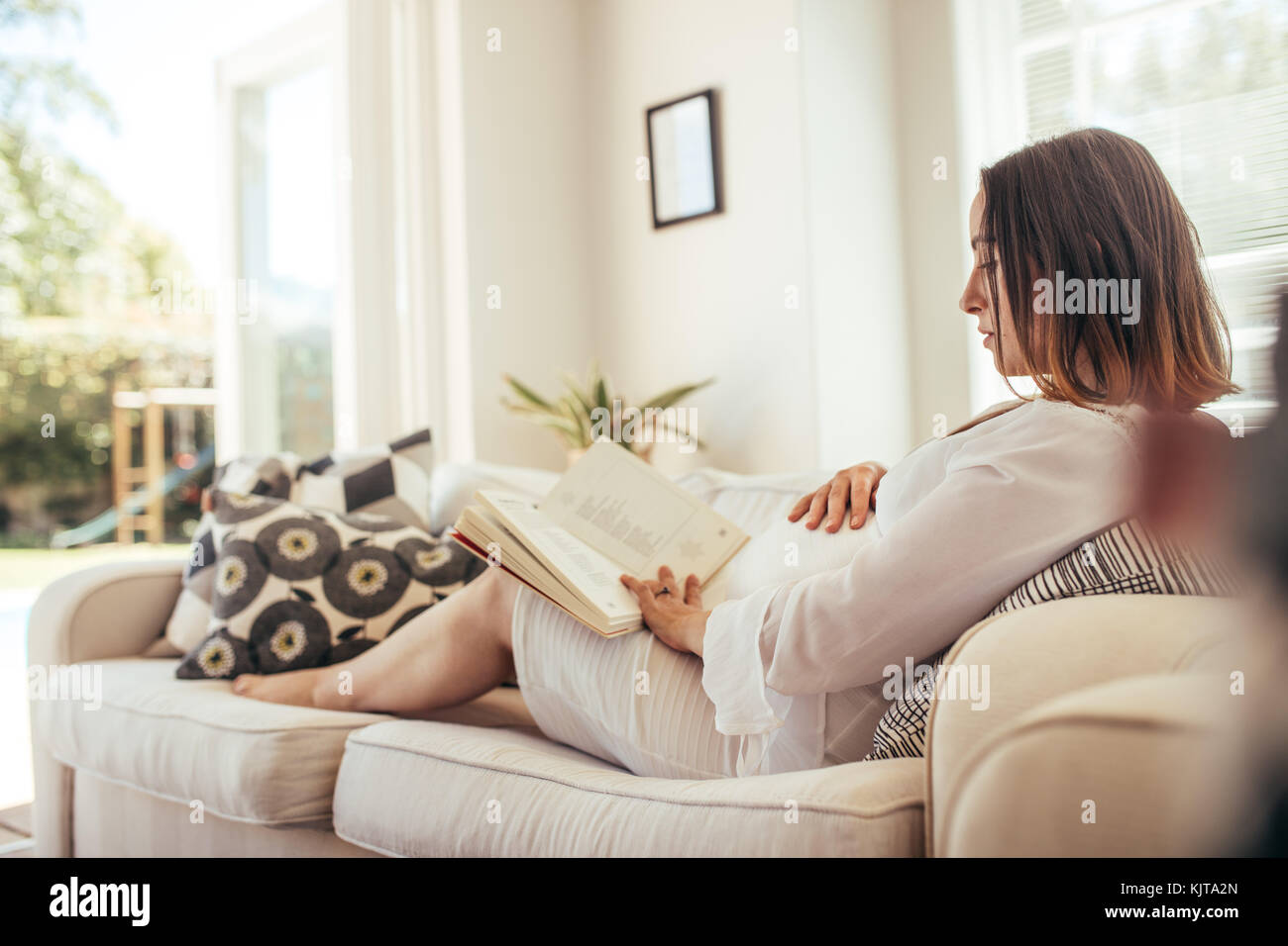 Pregnant woman sitting on sofa touching her belly and reading book. Expecting mother relaxing on sofa ready a book. - Stock Image