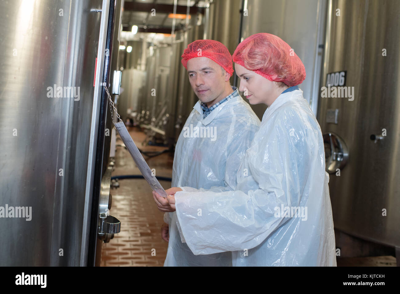 smiling farm employees working in raw milk factory Stock Photo