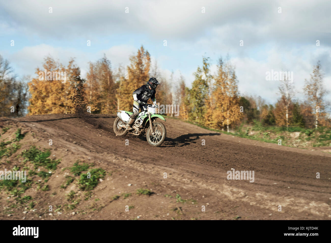 Motocross enduro rider in action accelerating the motorbike after the corner on dirt race track. Extreme off-road Stock Photo