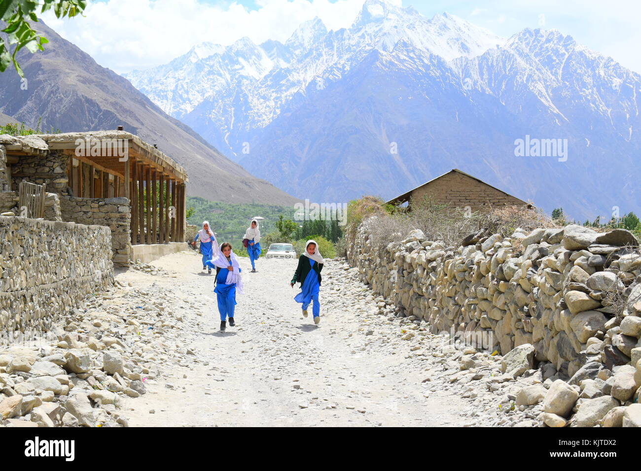 Happy local children on their way back to home after school. Playing and walking with joy, in the beautiful valley - Stock Image