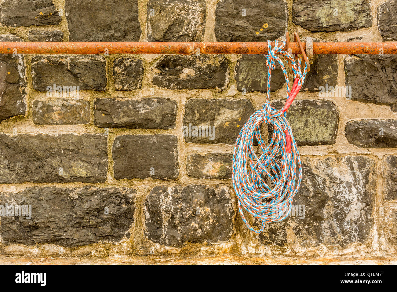 Rope hanging from a rusty rail. Stock Photo