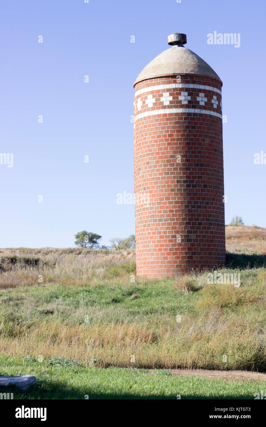 landscape picture of a old red brick grain silo in a green and