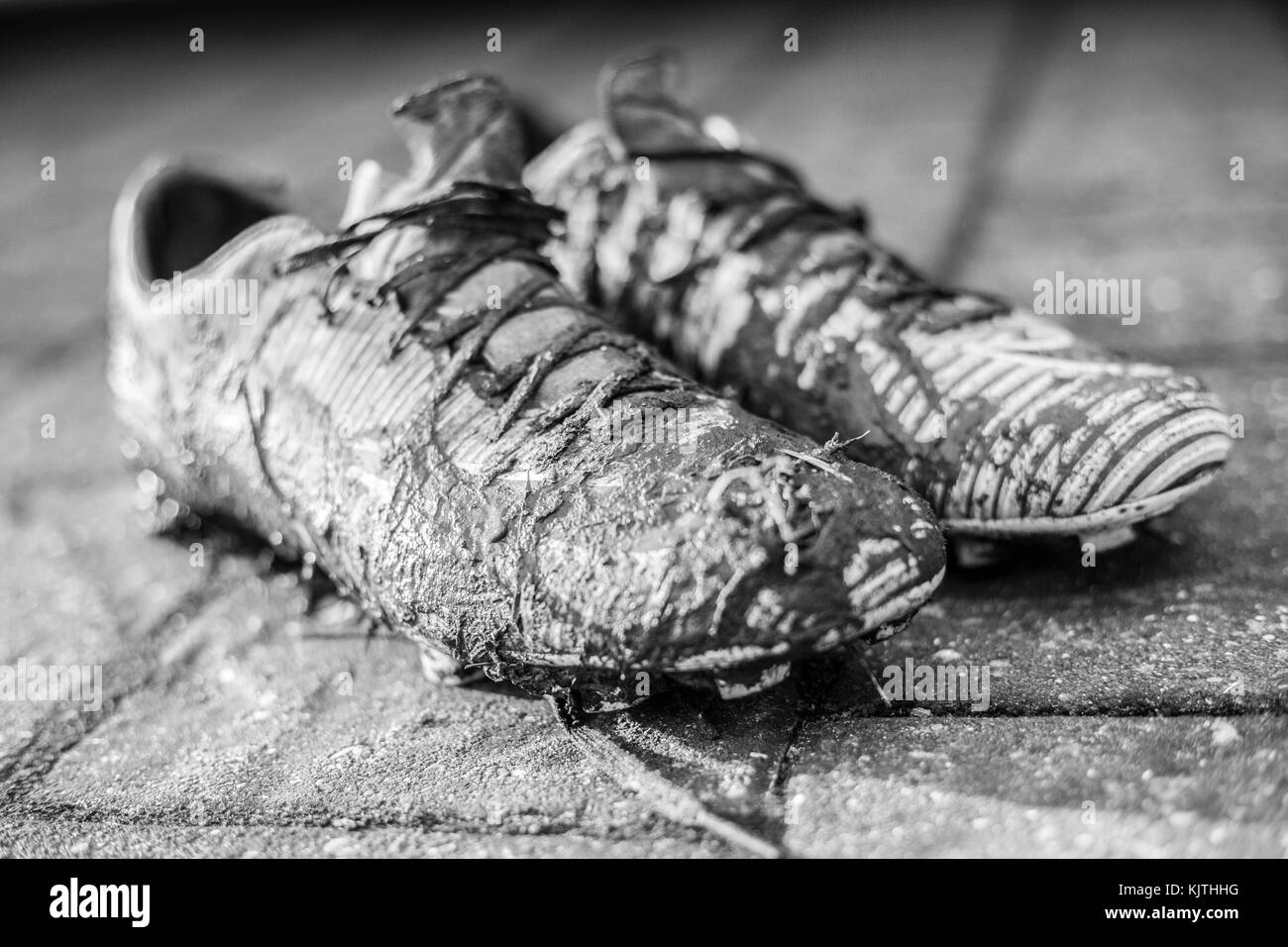 Black & white image of a pair of junior football boots heavily covered in mud - Stock Image