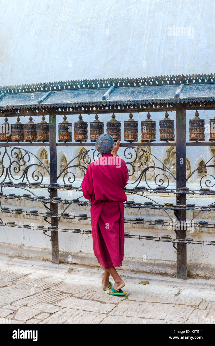 Monk turning Prayer Wheels, Swayambunath or Monkey Temple, Unesco World Heritage Site, Kathmandu, Nepal, Asia - Stock Image