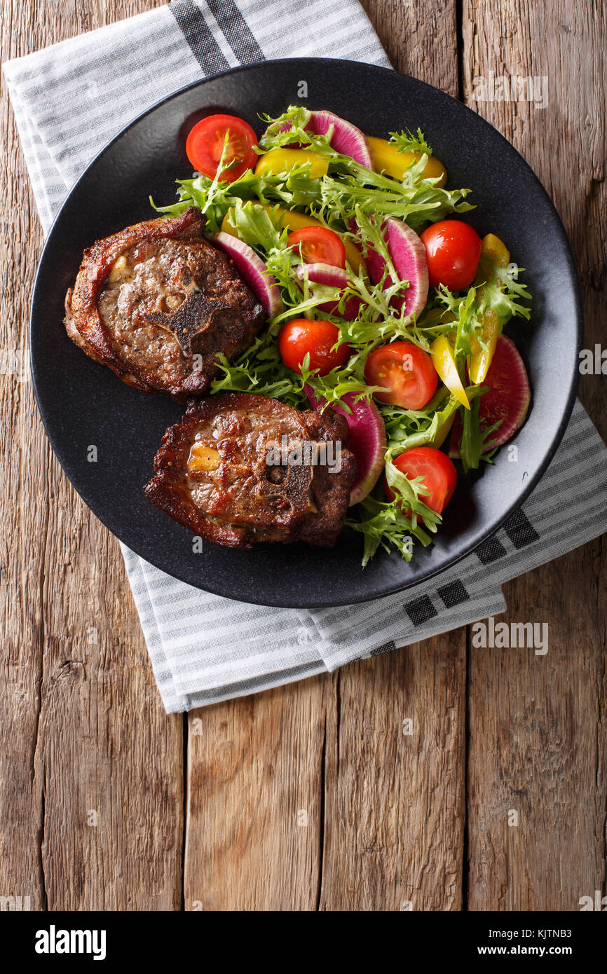Spicy delicious lamb steak and vegetable salad from radish, tomatoes, pepper and lettuce close-up on a plate. Vertical Stock Photo