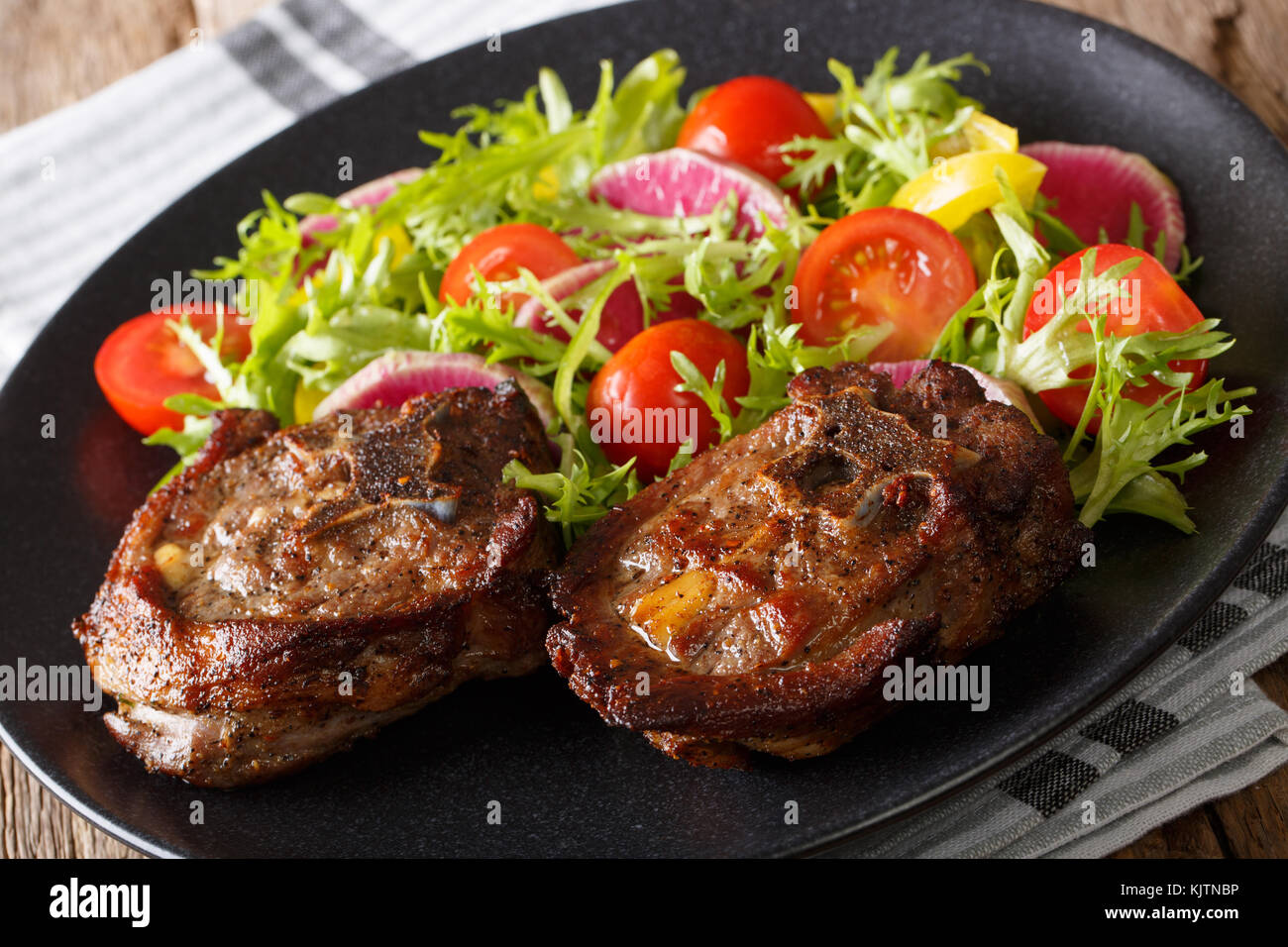 Roasted lamb steak and vegetable salad from radish, tomatoes, pepper and lettuce close-up on a plate. horizontal - Stock Image