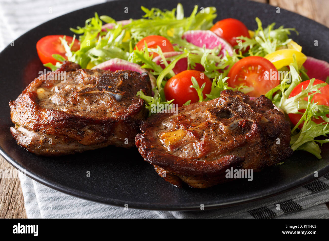 Spicy delicious lamb steak and vegetable salad from radish, tomatoes, pepper and lettuce close-up on a plate. horizontal - Stock Image