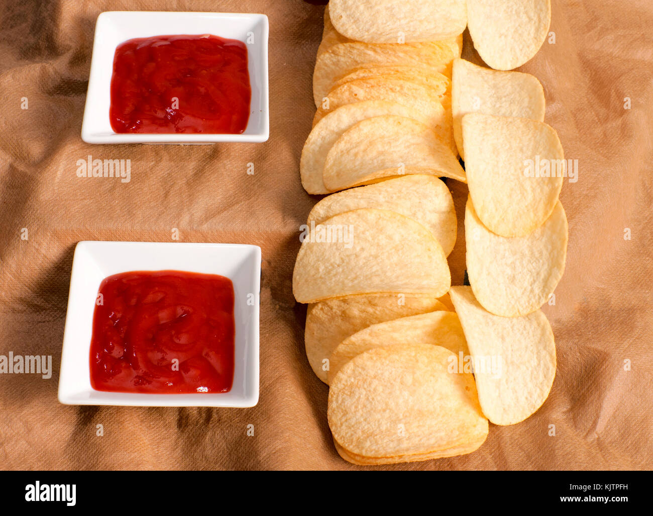 Potato chips and ketchup shoot in low key technique - Stock Image