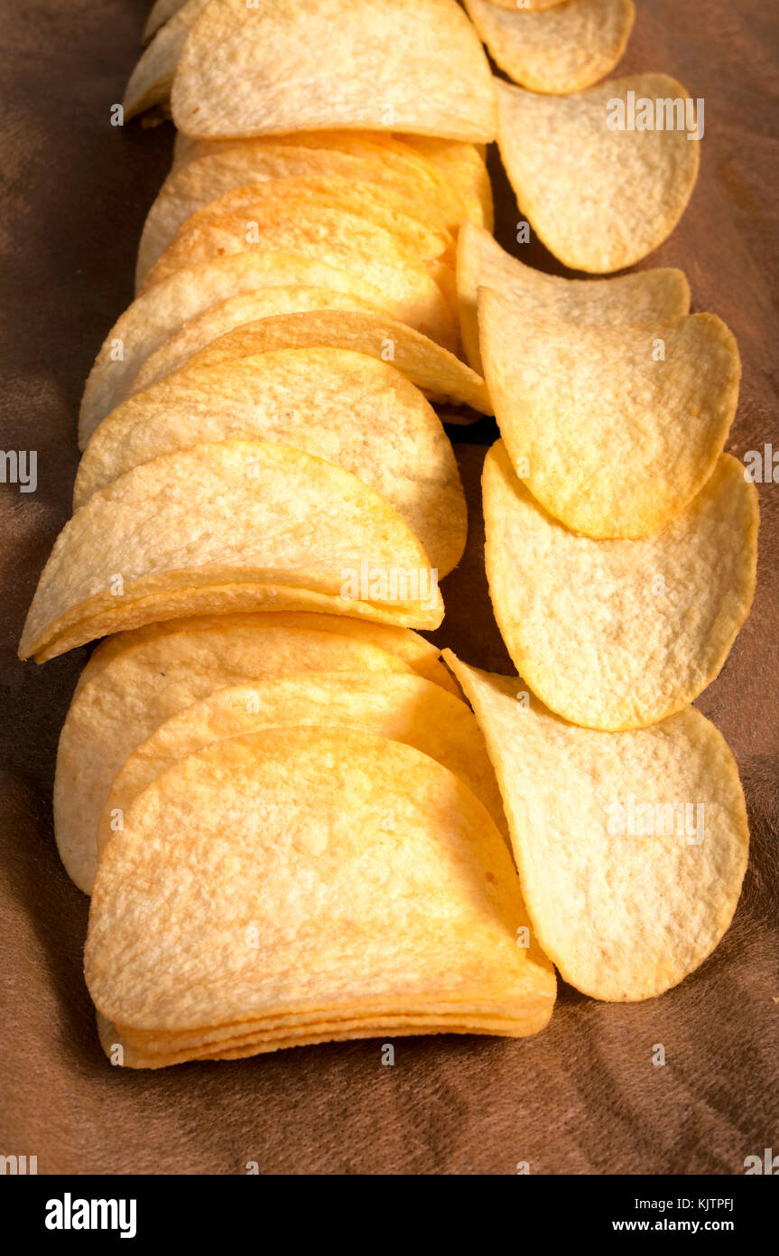 Potato chips in the line. Selective focus on the front chips - Stock Image