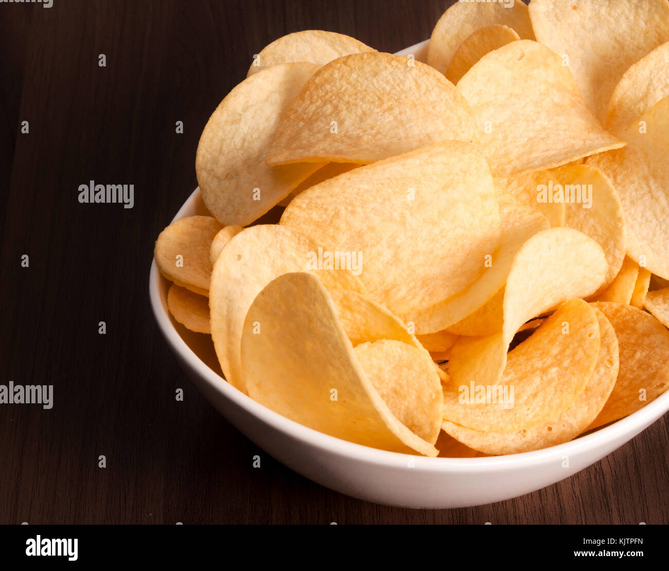 Potato chips in the white cup in low key - Stock Image