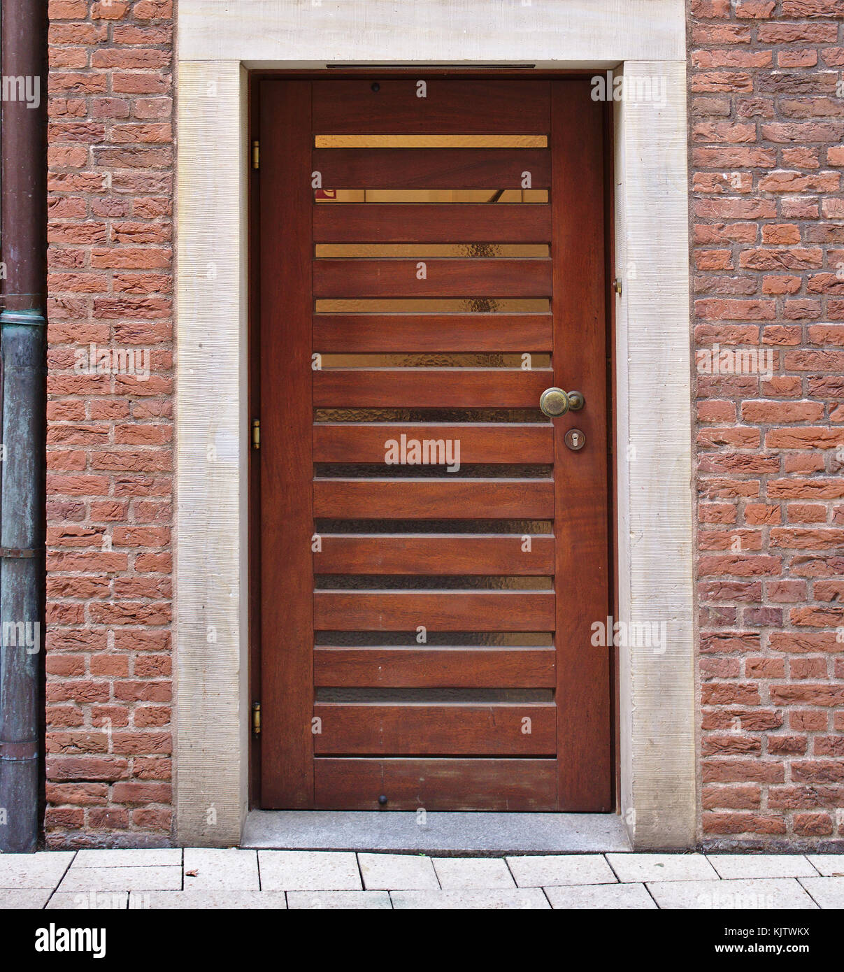 Modern Wooden Door In Red Brick Wall With Narrow Horizontal Window Panes  And Downspout