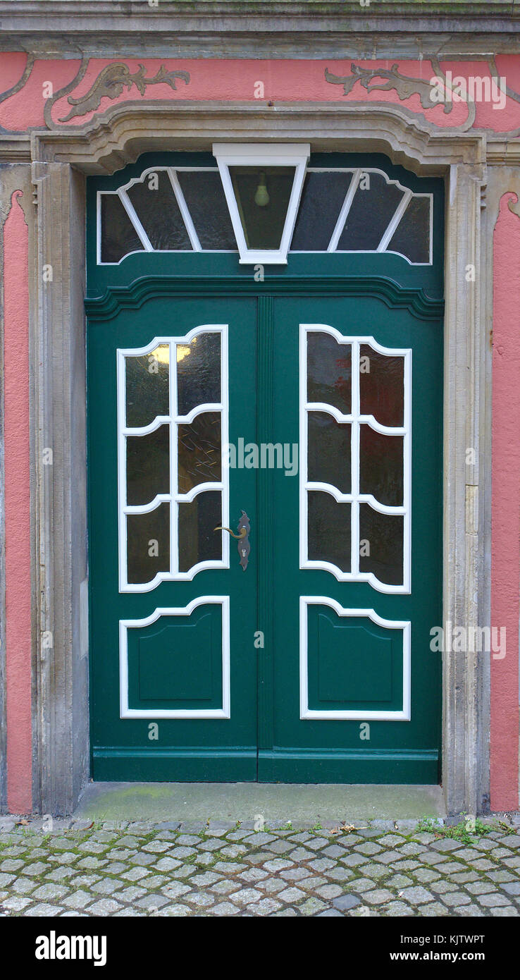 Dark green wooden door with white-framed window panes - Stock Image