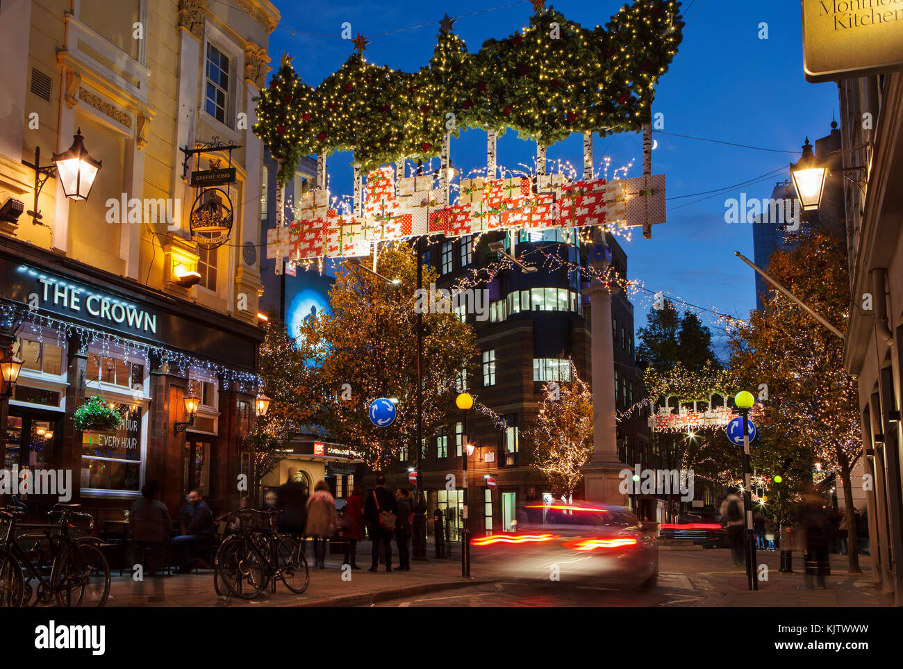 LONDON, UK - November 24th, 2017: Christmas lights on Seven Dials; seasonal lights are being displayed over busy - Stock Image