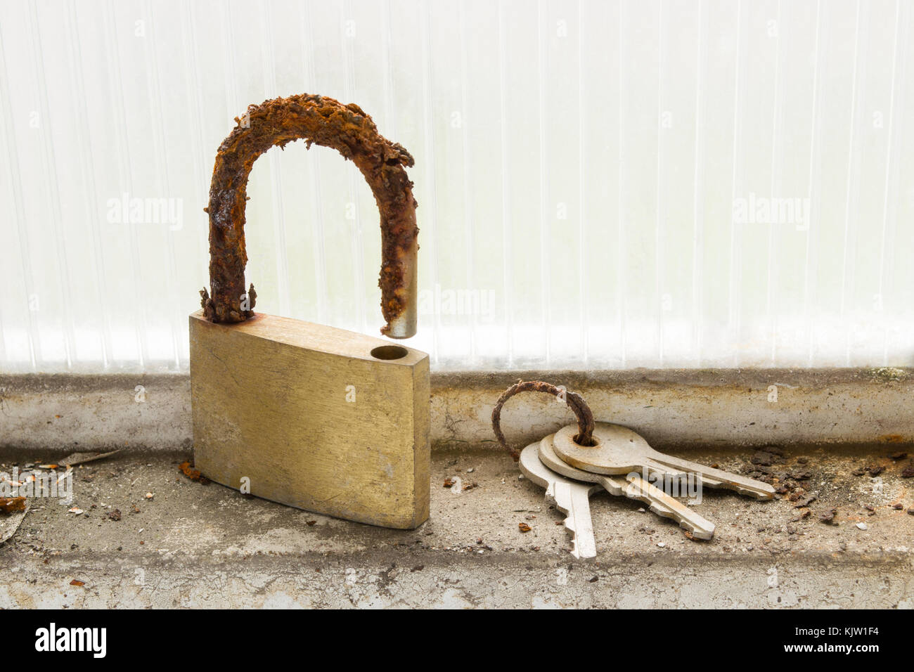 A lock and a set of keys look totally deteriorated and unusable due to the effect of the humidity and corrosion. - Stock Image