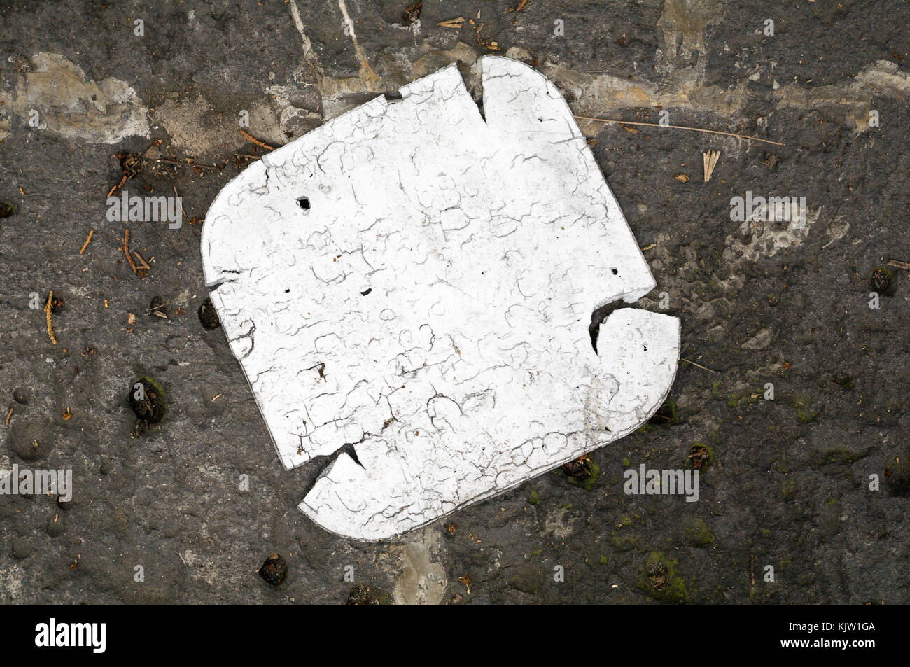 A disposable expanded polystyrene tray is lying on the sidewalk. Their deterioration demonstrates the indifference - Stock Image