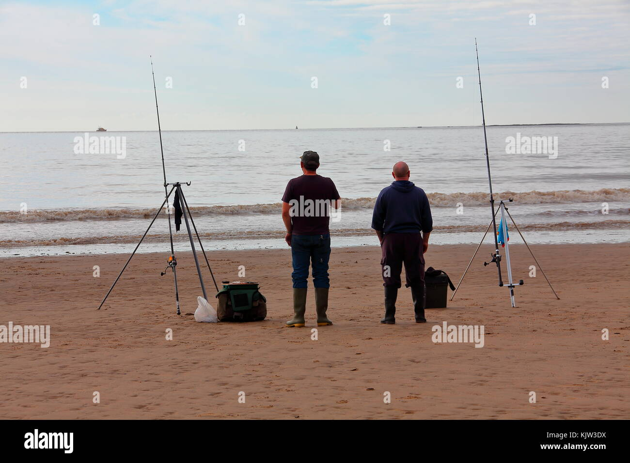 Two fishermen standing on the beach at low tide with fishing rods propped up on tripods waiting for a 'bite' - Stock Image