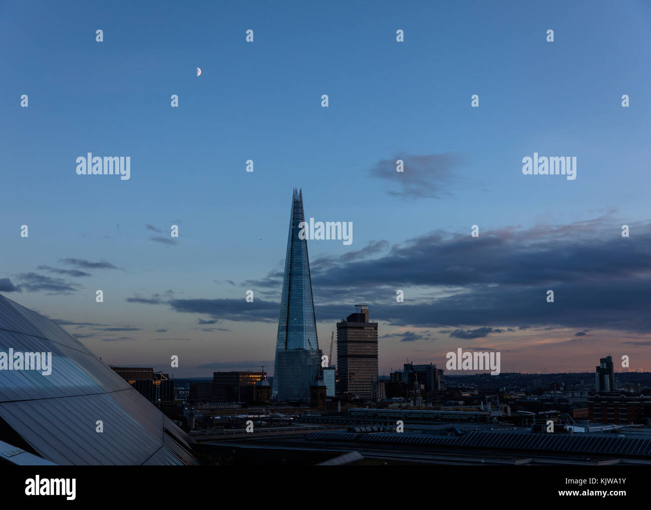 London, UK. 26th November, 2017. UK weather. Beautiful sunset on a cold, sunny winter day. Viwe of Shard, with moon - Stock Image