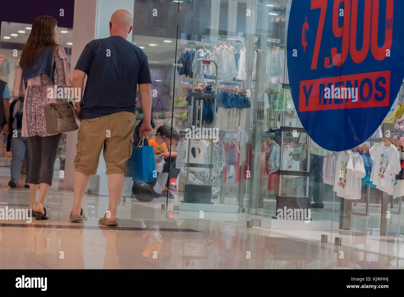 People walking through mall with shopping bags. Personas en centro comercial, bolsas de compras. photo by: Roberto Stock Photo