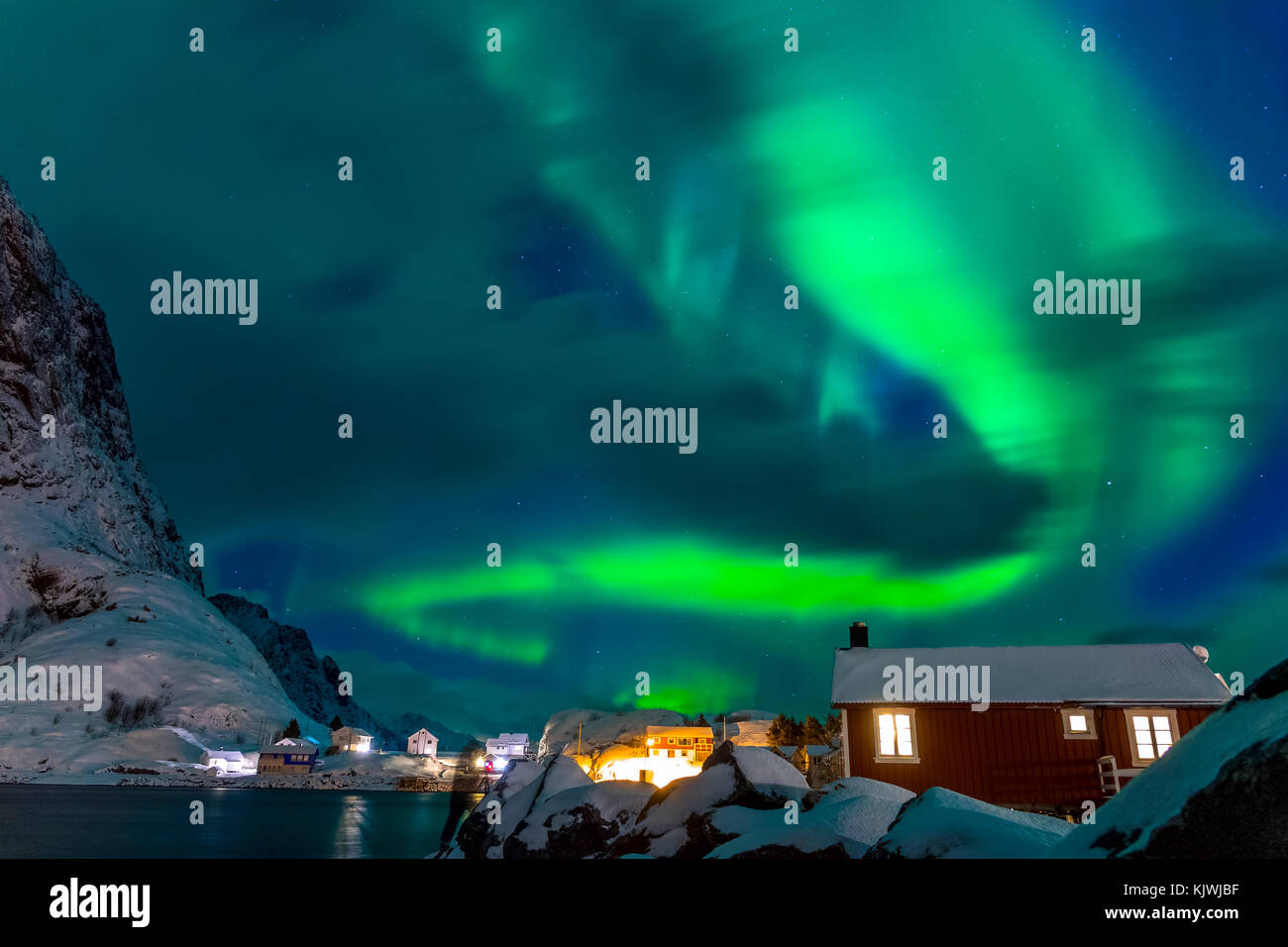 Winter Norway. Lofoten. Hamnoya town. Aurora Borealis above the roofs of houses - Stock Image