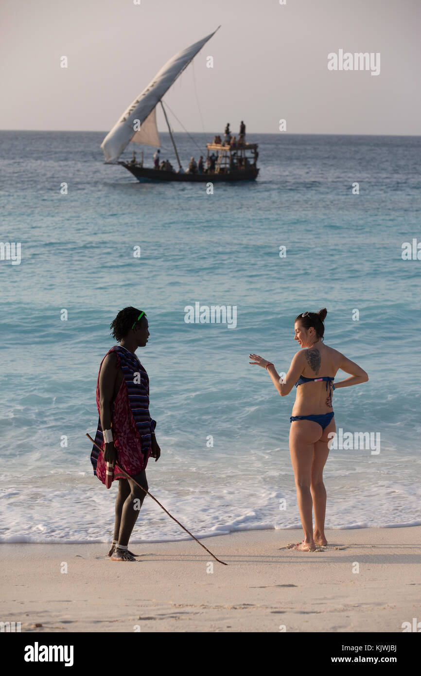 Zanzibar, Tanzania; A young Maasai warrior chats with a tourist by her beach hotel in the north of the island. - Stock Image