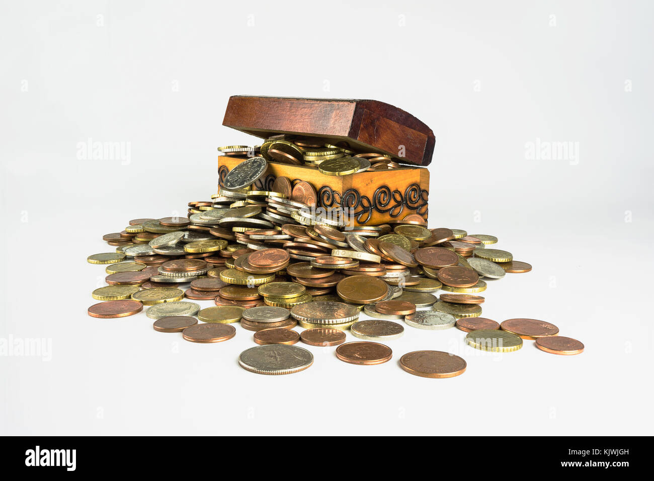 A small wooden treasure chest which is bursting with coins on a white background. Isolated composition which is - Stock Image