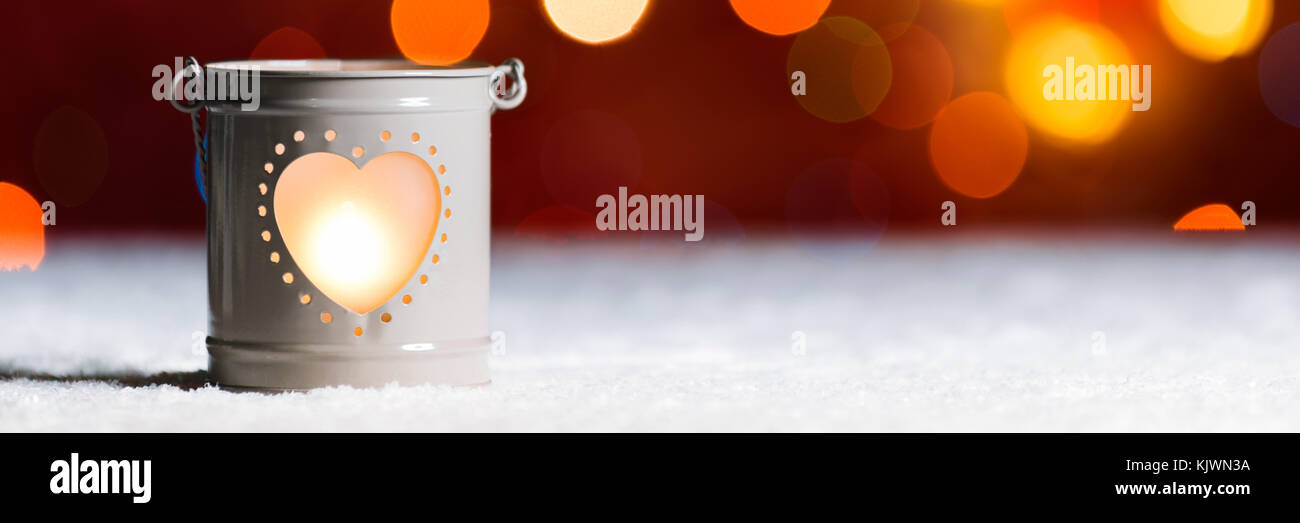 Burning candle in snow, with Christmas lights bokeh. Festive Christmas web banner with copy space - Stock Image