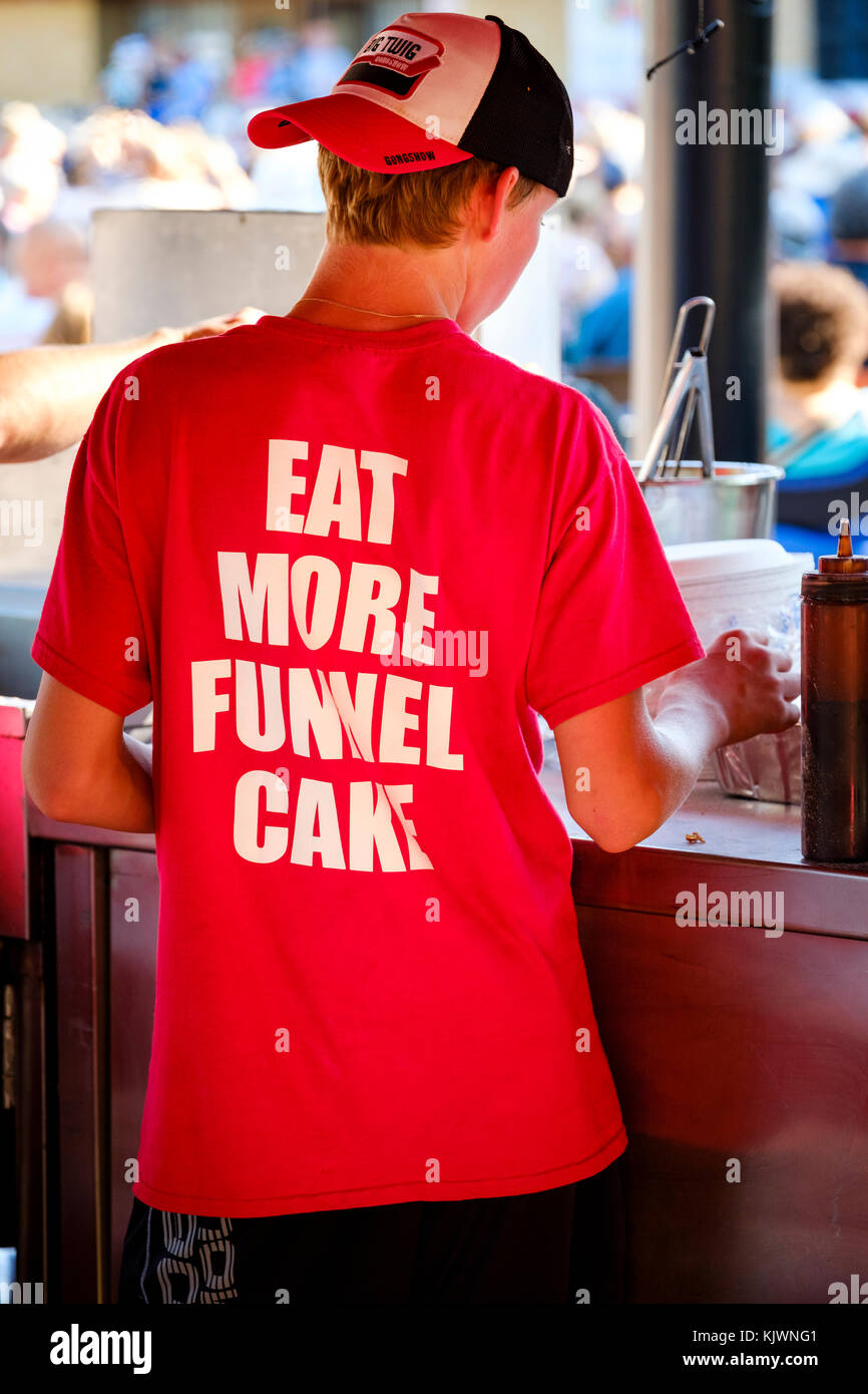 Funnel cake vendor working on food stall, back to the camera, promotional message on t-shirt. - Stock Image
