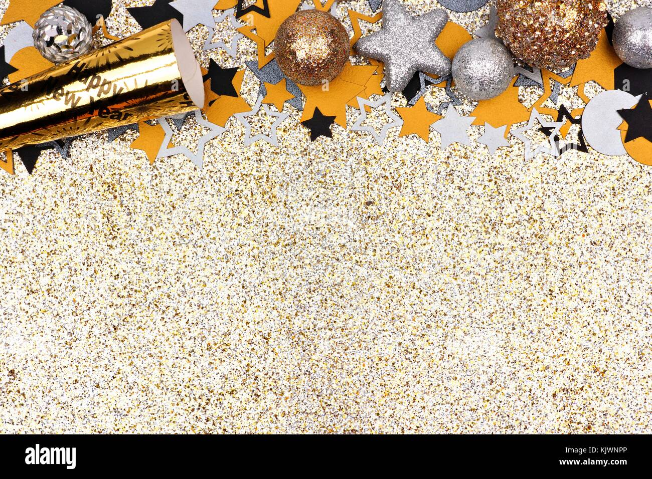 new years concept top border with confetti baubles and party noisemaker against a glittery gold