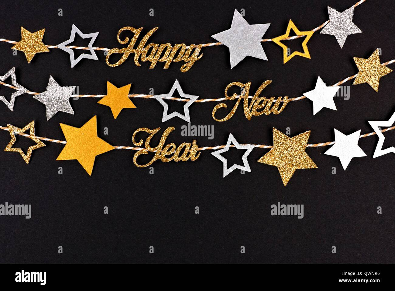 happy new year glitter text banner with strings of gold and silver stars against a black paper background