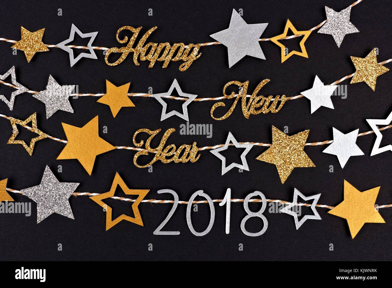 happy new year 2018 glitter text banner with strings of gold and silver stars against a black paper background