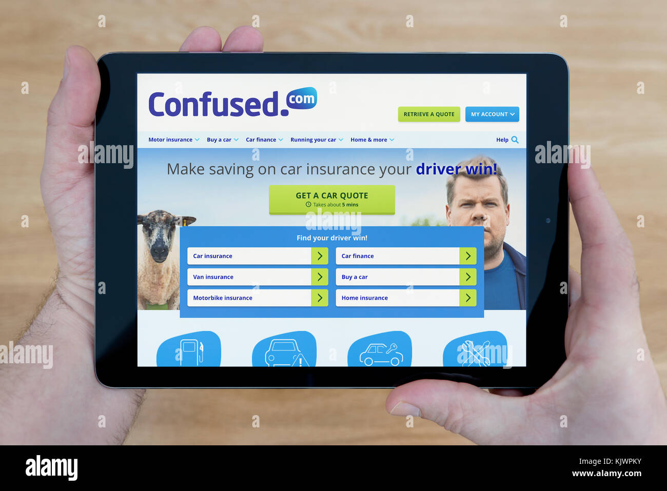 A man looks at the confused.com website on his iPad tablet device, shot against a wooden table top background (Editorial - Stock Image