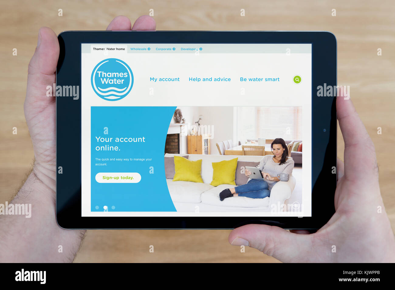 A man looks at the Thames Water website on his iPad tablet device, shot against a wooden table top background (Editorial - Stock Image