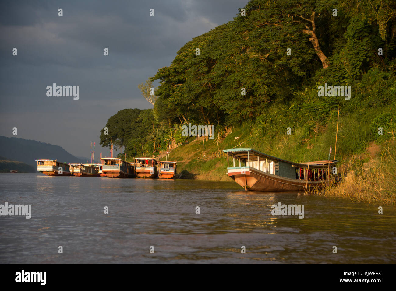 Boats in the evening sun on Mekong river in Luang Prabang - Stock Image
