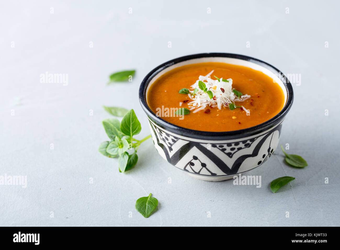 Pureed tomato soup in a bowl garnished with cheese and basil - Stock Image