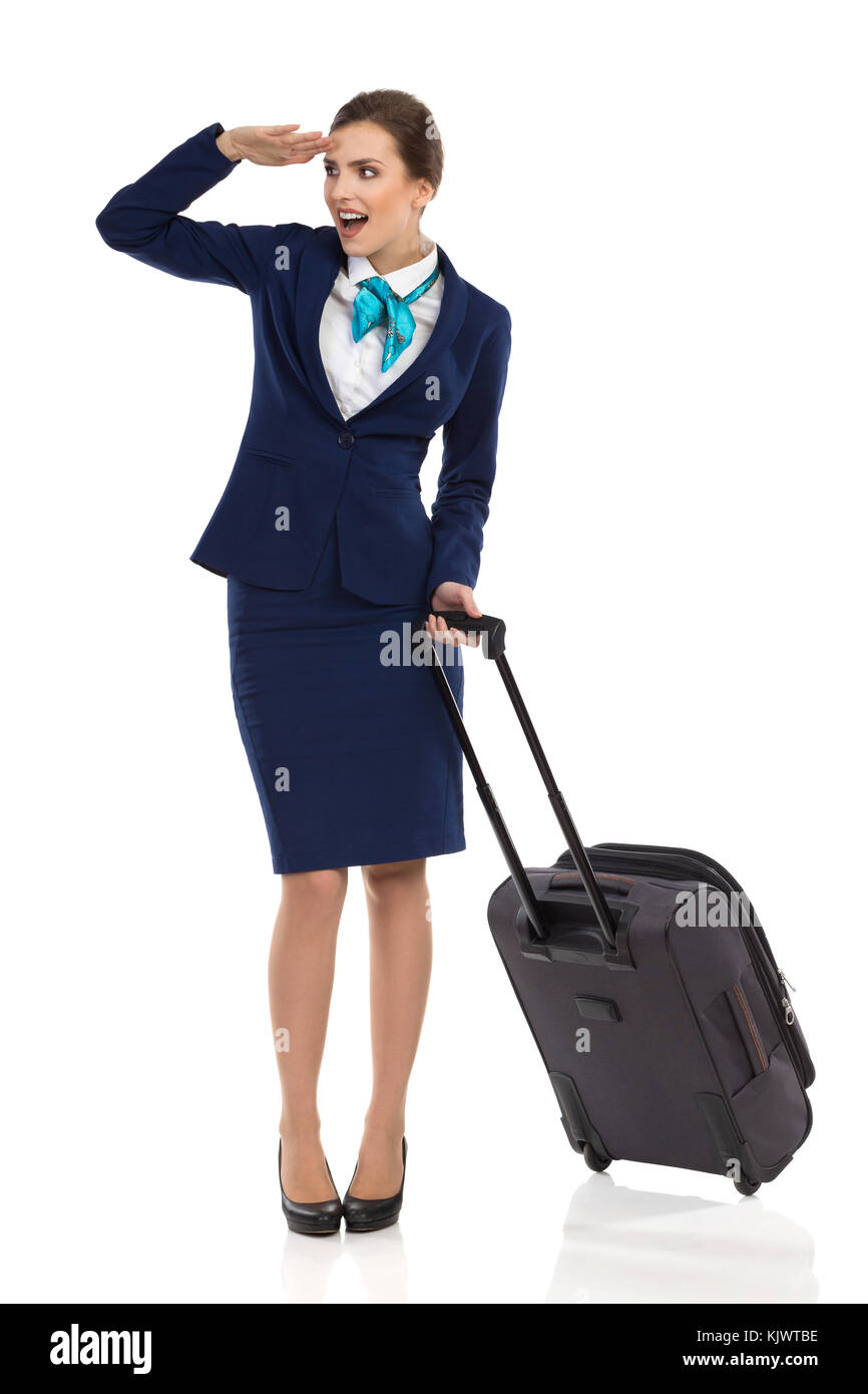 Ecstatic woman in blue suit and skirt is standing with trolley bag, holding hand on forehead, looking away and talking. - Stock Image
