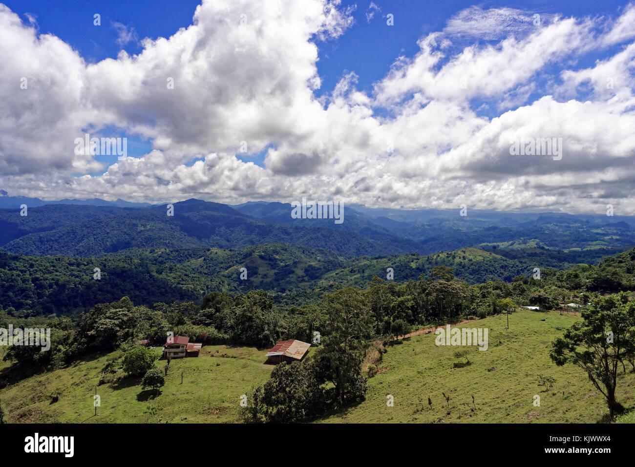 The mountain range Cordillera de Talamanca provides scenic views on meadows, farmhouses. Some clouds in the sky. - Stock Image